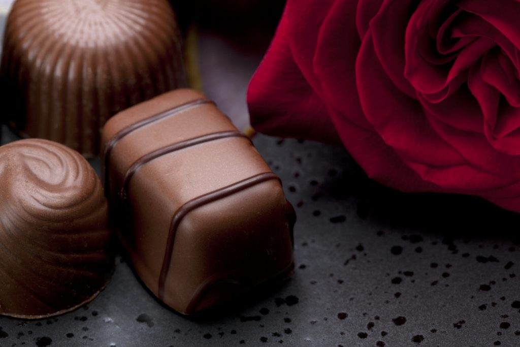 Chocolate candy on dish with rose.